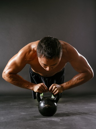 Photo of a muscular Asian man doing pushups with a kettlebell  photo