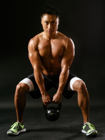 Photo of a muscular Asian man doing squats while holding a kettlebell  photo