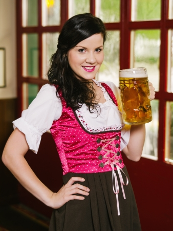 dirndl dress: Photo of a beautiful woman wearing traditional dirndl and drinking a huge beer. Stock Photo