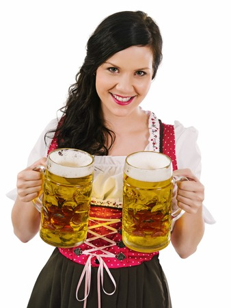 Photo of a beautiful woman wearing traditional dirndl and serving beer. photo