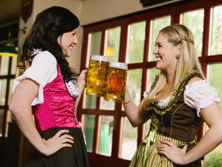 Photo of two beautiful woman wearing traditional dirndl and drinking beer.  photo