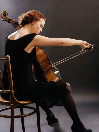cellist: Photo of a beautiful woman playing a cello. Stock Photo