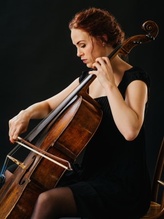 Photo of a beautiful woman playing an old cello. photo