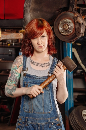 Photo of a young beautiful redhead mechanic wearing overalls and holding a huge rubber mallet.  Attached property release is for arm tattoos.  photo