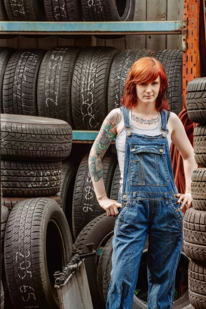 Photo of a young beautiful redhead mechanic wearing overalls and standing in an old garage. Attached property release is for arm tattoos.  photo