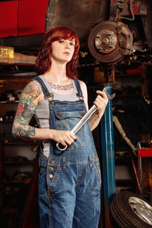Photo of a young beautiful redhead mechanic wearing overalls and holding a huge wrench.  Attached property release is for arm tattoos.  photo