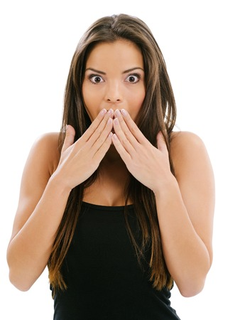 Photo of a beautiful woman with her hands over her mouth and eyes wide from shock. photo