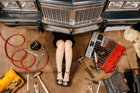 A woman wearing a black skirt and heels doing repairs under the front of an old car from the early 80's. photo