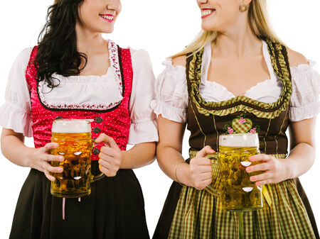 Photo of two woman wearing traditional dirndl and drinking beer. photo
