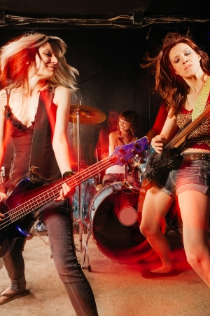 Photo of a rock and roll band playing on a stage. Female guitarist, bassist and drummer. Shot with strobes and slow shutter speed to create lighting atmosphere and blur effects. Slight motion blur on performers. photo