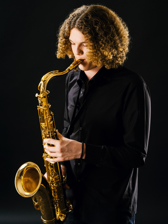 Photo of a teenager playing the saxophone over dark background. photo