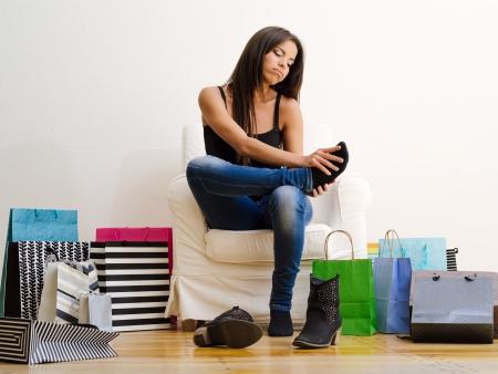 pies sexis: Foto de una joven y bella mujer sentada en una silla, rodeado de bolsas de la compra y frotando sus doloridos pies.