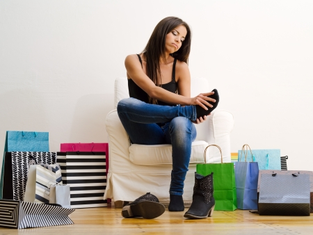 Photo of a young beautiful female sitting on a chair surrounded by shopping bags and rubbing her sore feet. Stock Photo