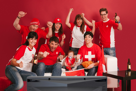 Photo of Swiss sports fans watching television and cheering for their team. photo