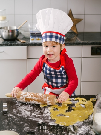 rolling: Photo of an adorable boy in a chef hat and apron using a rolling pin and making cookies in the kitchen.