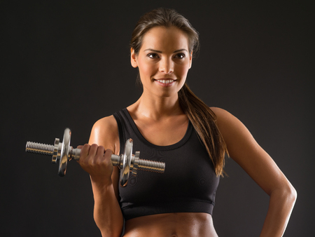 Photo of a toned young female exercising with dumbbells. photo