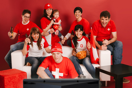 Photo of Swiss sports fans watching television and cheering for their team. Stock Photo - 24901341