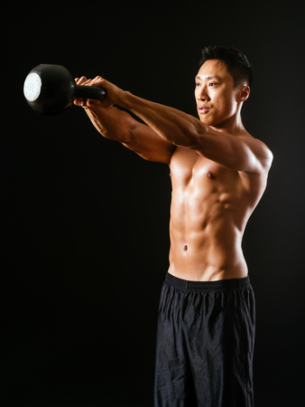 Photo of an Asian male exercising with a kettle bell over dark background.  photo