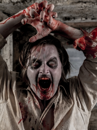 about you: Photo of a hungry zombie covered with blood about to attack you.  Stock Photo