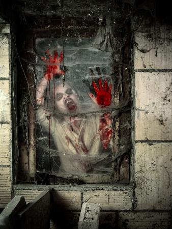 dientes sucios: Foto de un zombi hambriento cubierto de sangre junto a la ventana. Foto de archivo