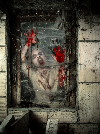 Photo of a hungry zombie covered with blood at the window. Stock Photo