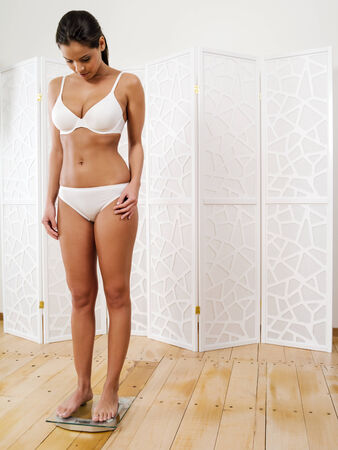 stepping: slim young woman in her underwear stepping on a scale.