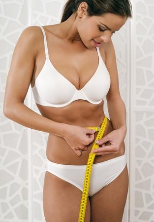 woman measuring waist: slim young happy woman in her underwear measuring her waist.