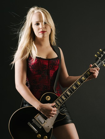 dark blond: sexy blond female playing a black electric guitar wearing a red corset.   Stock Photo