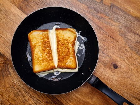 melted cheese: grilled cheese sandwich cooking in a large frying pan.   Stock Photo