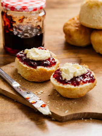 scone: delicious scones on a plate with clotted cream and jam.   Stock Photo