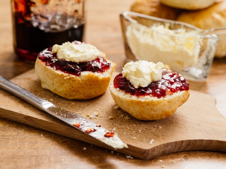 delicious scones on a plate with clotted cream and jam.