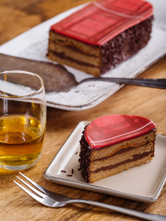 dram: slice of Scottish whisky cake and a dram of whisky on top of a wood table.