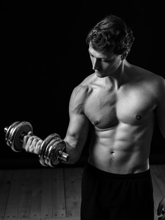 early thirties: a man in his early thirties doing bicep curls with a dumbbell over a black. Black and white version.