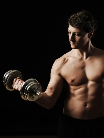 early thirties: a man in his early thirties doing bicep curls with a dumbbell over a black.