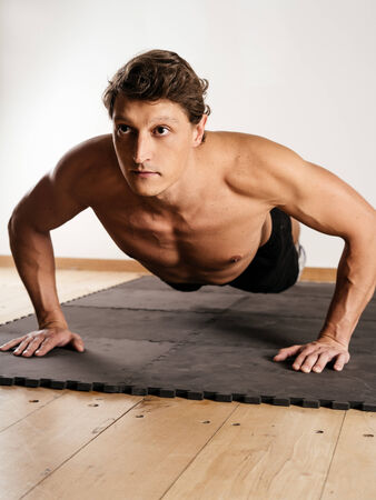 early thirties: a man in his early thirties doing pushups on a mat in a fitness centre.   Stock Photo