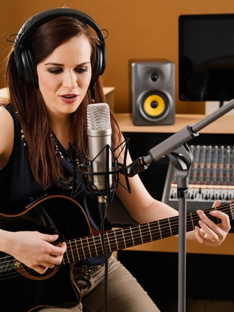 Photo of a beautiful brunette in a recording studio playing an acoustic guitar and singing into a large diaphragm microphone.