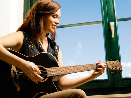 late twenties: Photo of a smiling woman in her late twenties playing an acoustic guitar by a large window. Stock Photo