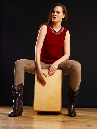 Photo of a beautiful young woman playing a Cajon percussion instrument.