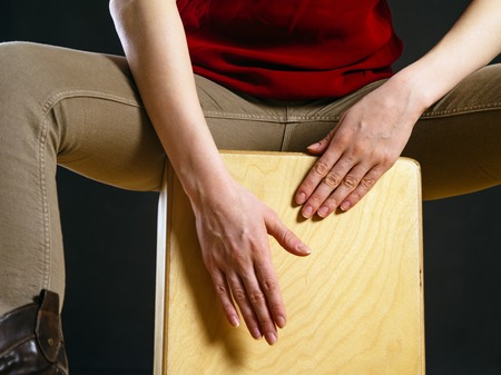Closeup photo of a woman playing a Cajon percussion instrument.