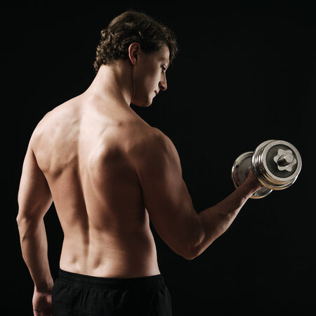 early thirties: Photo of a man in his early thirties doing bicep curls with a dumbbell over a dark wall