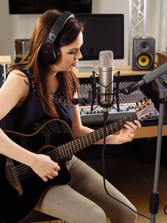 vocalist: Photo of a beautiful brunette in a recording studio playing an acoustic guitar and singing into a large diaphragm microphone.