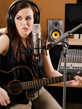 vocalist: Photo of a beautiful brunette in a recording studio uncertain about the quality of her playing