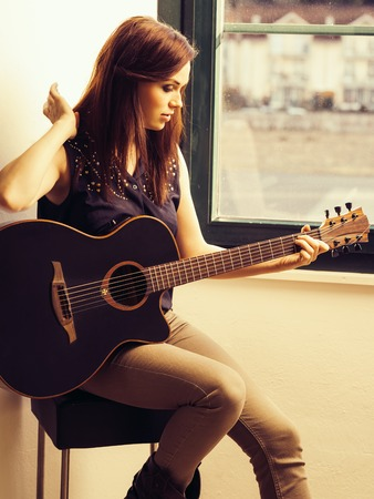 Photo of a woman playing an acoustic guitar while sitting by a window