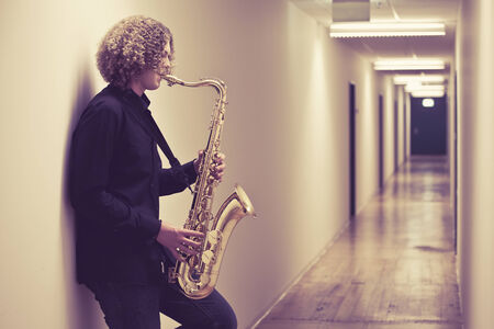 Photo of a young man playing the saxophone in a hallway. Heavily filtered.  photo