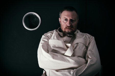 Photo of an insane man in his forties wearing a straitjacket standing in a cell of an asylum with the light from the hallway streaming in. photo