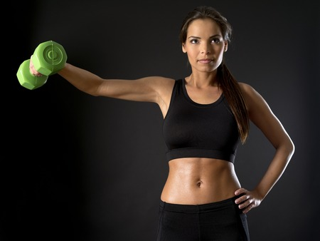 woman lifting weights: Photo of a beautiful female doing a side shoulder fly with a dumbbell over a dark background. Stock Photo