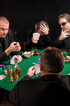 Photo of men playing poker, drinking and smoking, and looking uncertain of their luck. photo