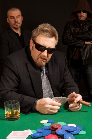 Photo of a man playing poker while wearing sunglasses and smoking a cigar.