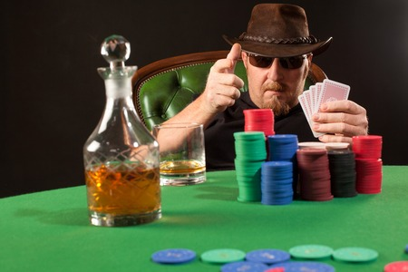 Photo of a man playing poker while wearing sunglasses and a hat.
