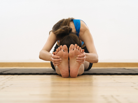 human toe: Photo of a woman in her twenties grabbing her feet and stretching her leg muscles. Focus is on the feet and hands.